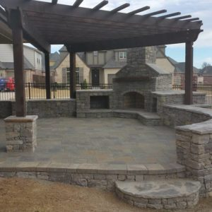 Patio & Retaining Wall Featuring an Outdoor Fireplace & Pergola